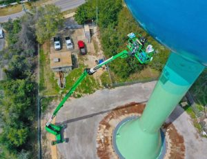 Even the comparatively simple tasks of roughing in background colors and attaching patterns with magnets are fraught with increased complexity at 180 ft. off the ground.
