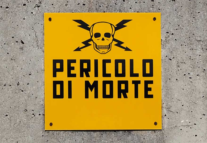 """This Italian sign, which translates to """"danger of death,"""" speaks the universal language of hazard signs: bright yellow paired with a bold black font, adorned with a skull and bolts of electricity."""
