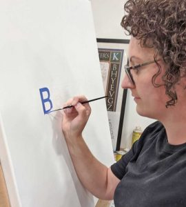 Konanz used a transfer patter and letters with enamel paint.