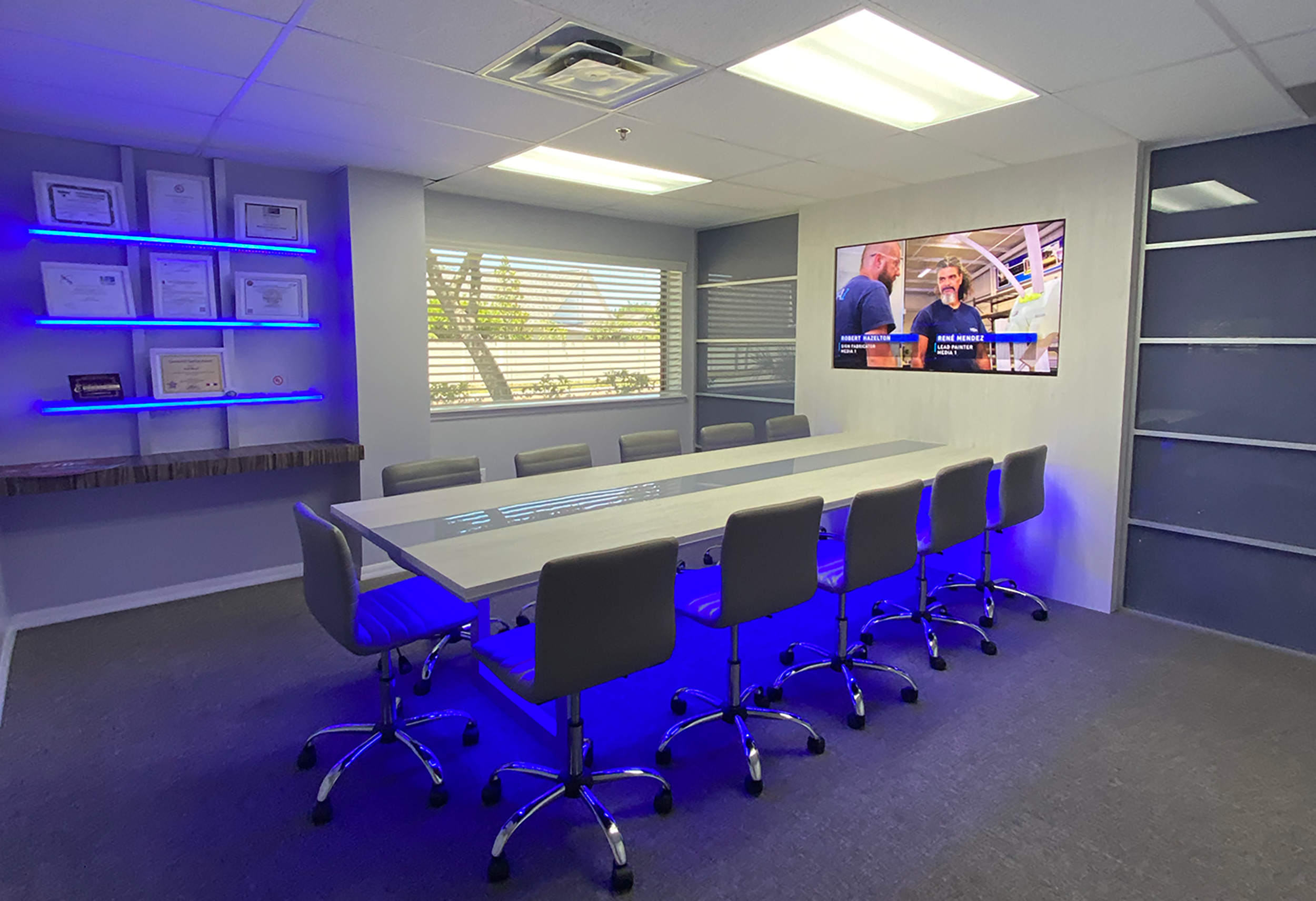Media 1/Wrap This' new conference room features a 4 x 11-ft. table mounted into an aluminum wall feature that includes a 65-in. flat screen TV. Blue LED modules are located below the table and in the shelving of the side walls.